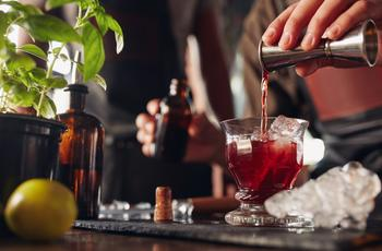 Bartender pours falernum syrup in cocktail