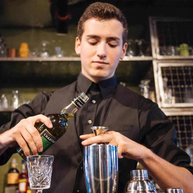 young professional bartender pouring