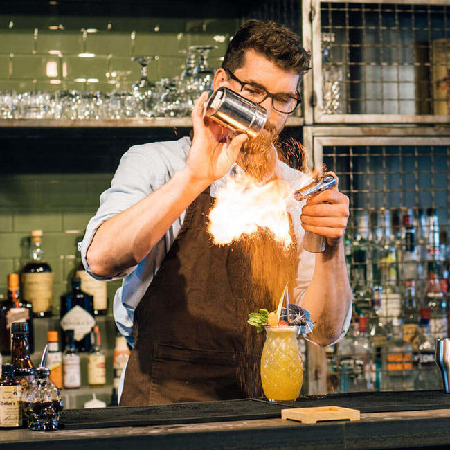bartender creating fire trick over cocktail