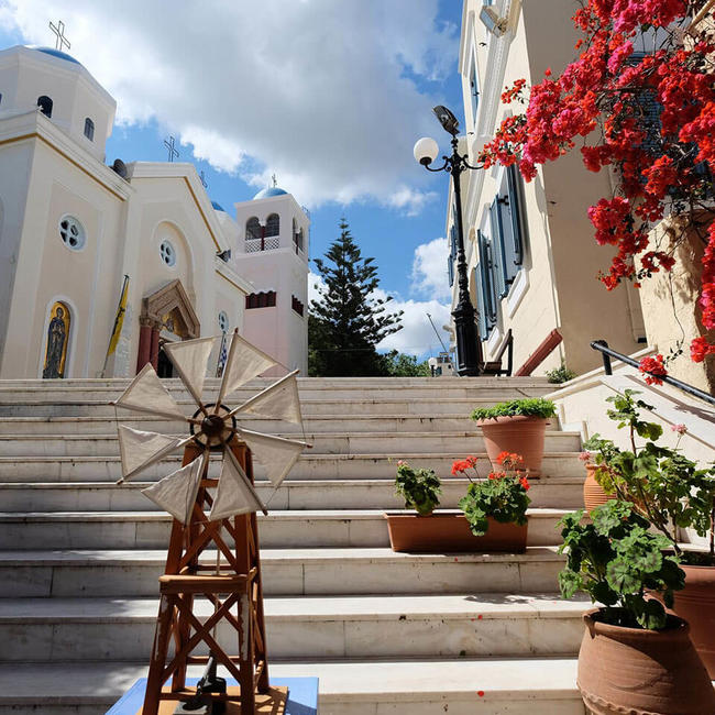 white building and steps with flowers in kos