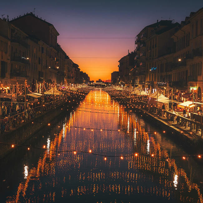 milan canals dimly lit by string lights at sunset