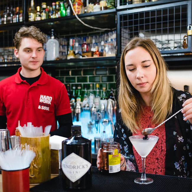 barman instructor supervising a student making a cocktail
